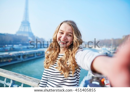 Beautiful young girl taking funny selfie with her mobile phone near the Eiffel tower