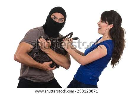 beautiful young girl taking hand bag from masked male thief isolated on white - stock photo
