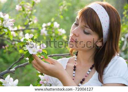 beautiful young girl tenderly looks at the flowers of apple