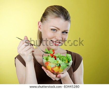 Beautiful young girl the blonde with a plate of fresh vitamin salad from vegetables