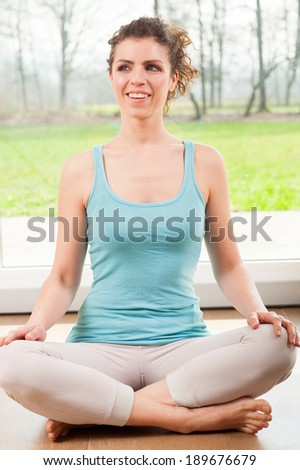Beautiful young girl training yoga in front of the window - stock photo