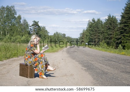 Beautiful young girl traveling with bag Sits on bus stop and reads book - stock photo