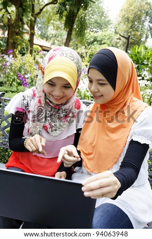 beautiful young girl using a notebook at garden with her friend - stock photo