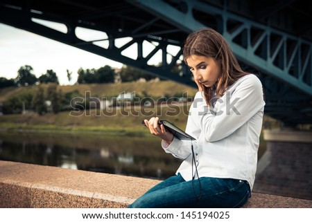Beautiful young girl using digital tablet outdoors - stock photo