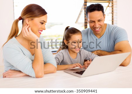 beautiful young girl using laptop with her parents at home - stock photo
