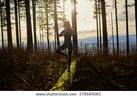 beautiful young girl walking in forest standing on log in yoga tree pose - stock photo