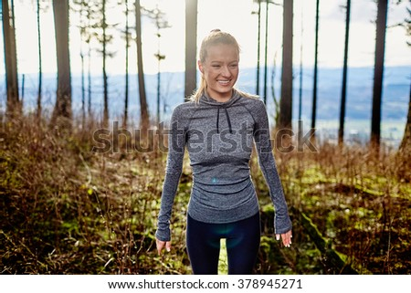 beautiful young girl walking in forest standing on log smiling - stock photo