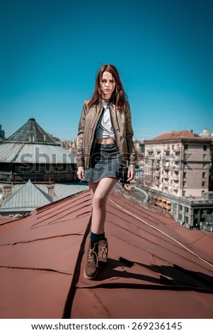 Beautiful young girl walking on the roof on big city background. - stock photo