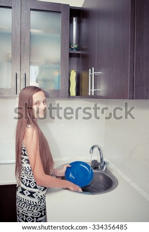 Beautiful young girl washing the dishes - stock photo