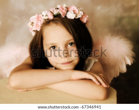Beautiful young girl wearing angel wings and floral halo - stock photo