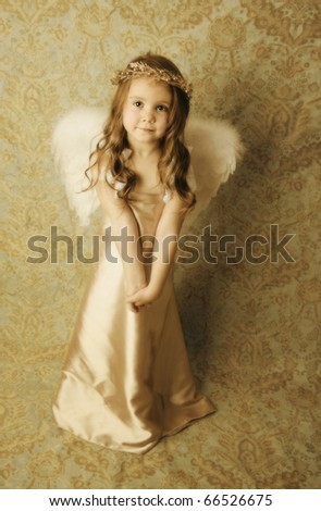 Beautiful young girl wearing angel wings and gold halo wreath with soft sweet smile expression, vintage look - stock photo