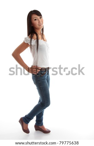 Beautiful young girl wearing skinny leg denim jeans and a white ruffled top.
