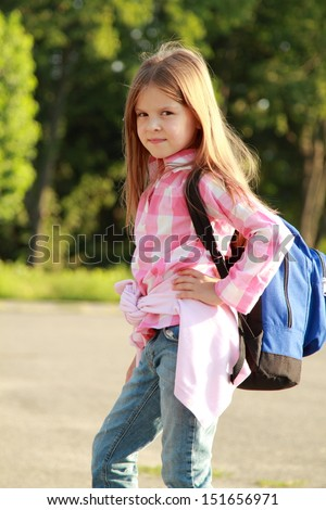 Beautiful young girl with a backpack exploring nature in biology class in the street/Schoolgirl with backpack goes to school - stock photo