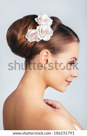 Beautiful young girl with a floral ornament in her hair. - stock photo