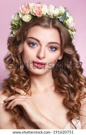 Beautiful young girl with a floral ornament in her hair.Beautiful Woman Touching her Face. Youth and Skin Care Concept.Nymph. Portrait of Genuine Gorgeous Woman in Wreath of Flowers - stock photo