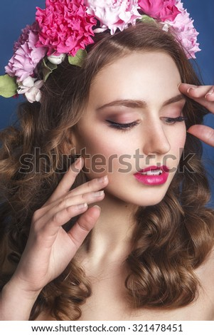 Beautiful young girl with a floral ornament in her hair on a blue background. Woman  in wreath of flowers.Beauty Face. Fashion photo.Perfect makeup. Skin care concept.