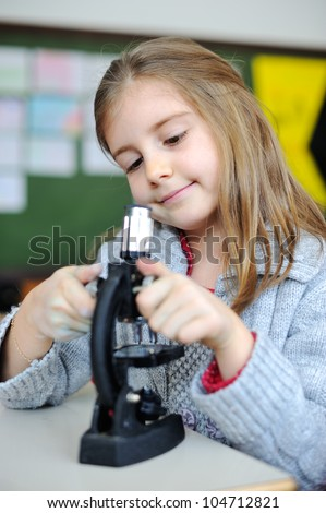 Beautiful young girl with a microscope - stock photo
