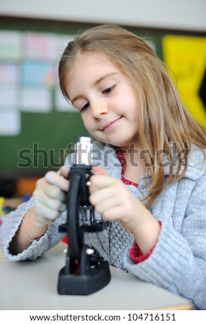 Beautiful young girl with a miscroscope - stock photo