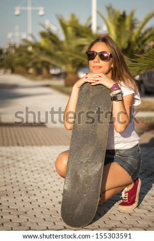 Beautiful young girl with a skateboard outdoor on summer