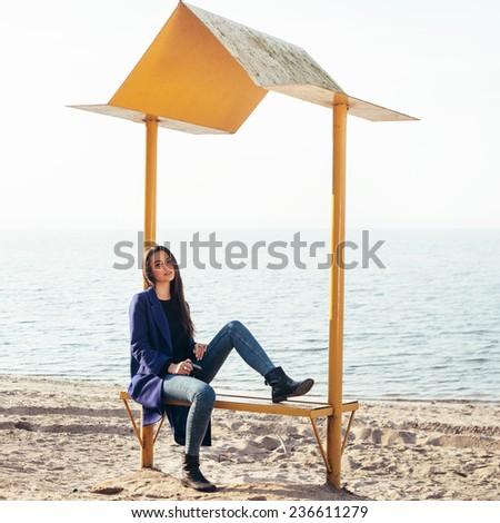 Beautiful young girl with an old camera in hand sitting on the beach near the sea and looking at the camera, sitting and waiting  - stock photo