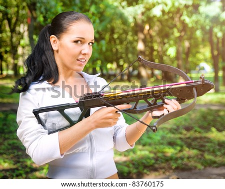beautiful young girl with arbalest on the wood background - stock photo
