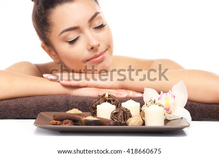 Beautiful young girl with aromatic candles and salt lying on brown towel, isolated on white - stock photo
