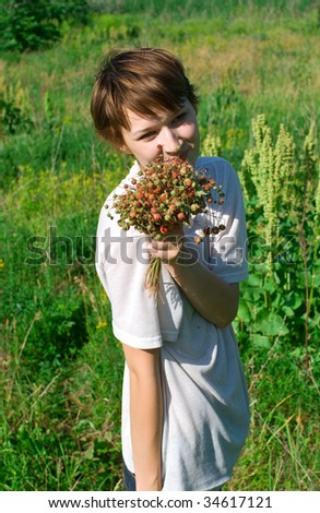 Beautiful young girl with aromatic wild strawberry against summer plants