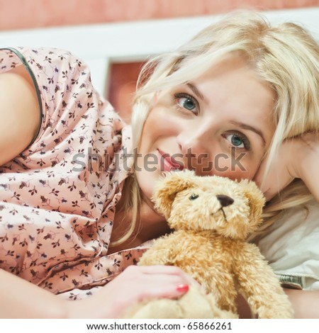 Beautiful young girl with bear toy in bed - stock photo