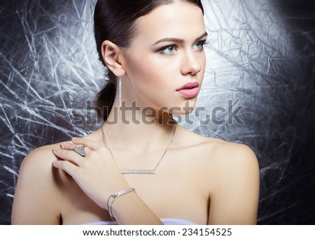 beautiful young girl with beautiful stylish expensive jewelry, necklace, earrings, bracelet, ring, filming in the Studio - stock photo