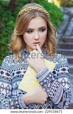 beautiful young girl with blond hair and blue eyes holding a book in his hands - stock photo