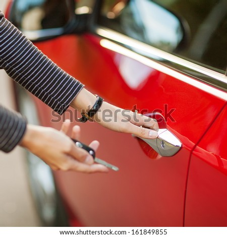Beautiful young girl with car key in hand and opens the car - stock photo