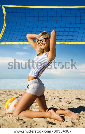 Beautiful young girl with colorful ball on beach. - stock photo
