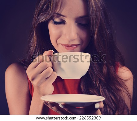 Beautiful young girl with cup of coffee on brown background - stock photo