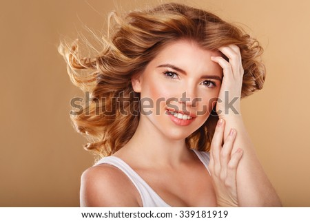 Beautiful young girl with curly hair straightens her hair. The girl smiles. Barber. Beauty salon. Beauty makeup. - stock photo
