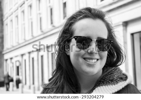 Beautiful, young girl with dark long hair and sunglasses, smiling in the streets of big city, in black and white. - stock photo