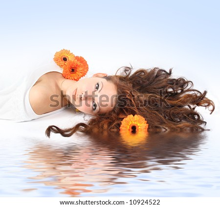 beautiful young girl with flowers is relaxing - stock photo