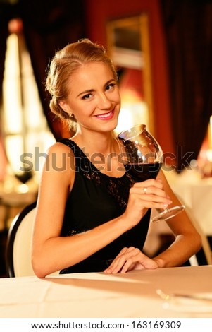 Beautiful young girl with glass of red wine alone in a restaurant - stock photo