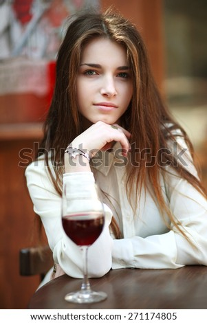 Beautiful young girl with glass of red wine, alone in a restaurant, outside  - stock photo