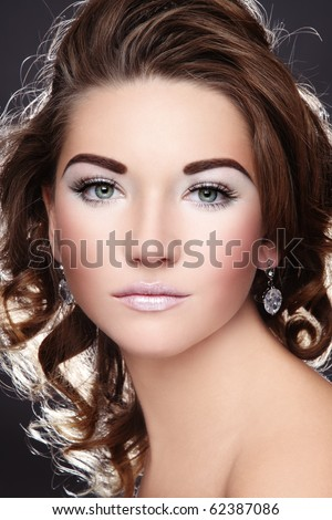 Beautiful young girl with glowing white make-up and curly hairstyle - stock photo