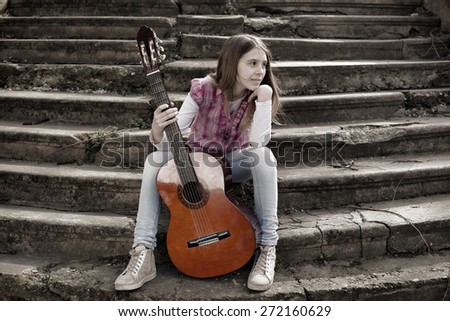 Beautiful Young Girl With Guitar Sitting on the Foot of the Stairs and Looking Thoughtfully at the Horizon - stock photo