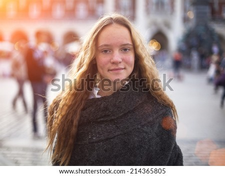 Beautiful young girl with her hair standing on the street, blurred background. - stock photo