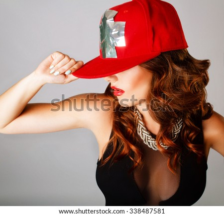 beautiful young girl with large breasts, red lipstick, red baseball cap dances his hand on the cap - stock photo