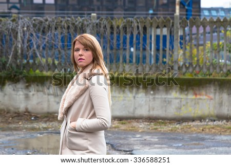 Beautiful young girl with long blond hair posing in an urban context - stock photo