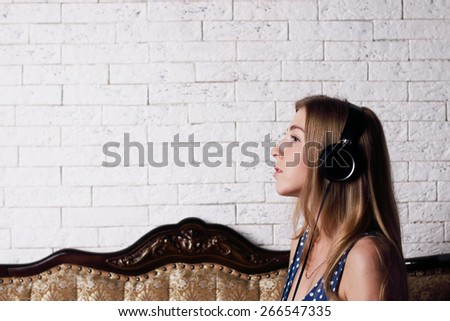 Beautiful young girl with long blond hair sitting on couch with headphones - stock photo