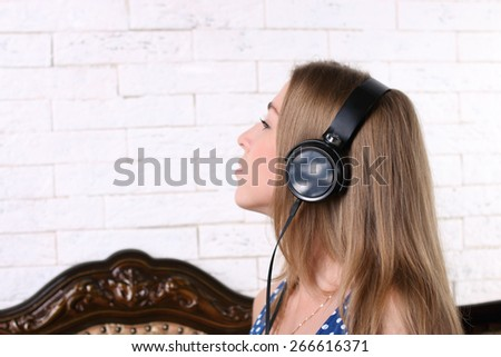 Beautiful young girl with long blond hair sitting with headphones