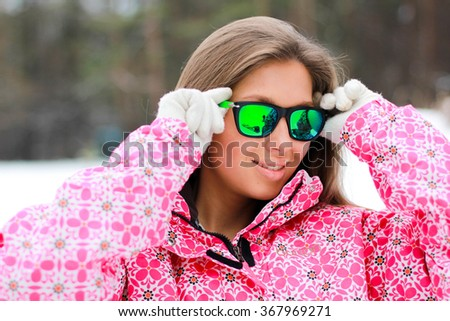 Beautiful young girl with long blond hair wearing sunglasses and a warm jacket winter sports resort in Courchevel, Alps