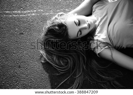 Beautiful young girl with long hair lying on the asphalt in the street during sunset. Portrait. Black and white - stock photo