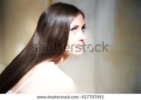 Beautiful young girl with long hair posing in bright light in a church. She is sad. probably she is thinking about human life