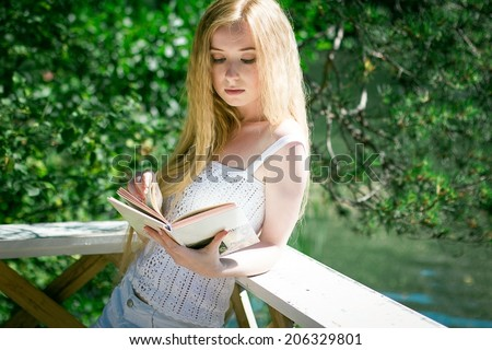 Beautiful young girl with long hair reading a book on nature