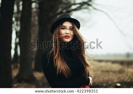 Beautiful young girl with long straight hair, light make-up in a stylish trendy in a black jacket and red leather skirt in black hat outdoors in a park on a background of trees. The girl looks  camera